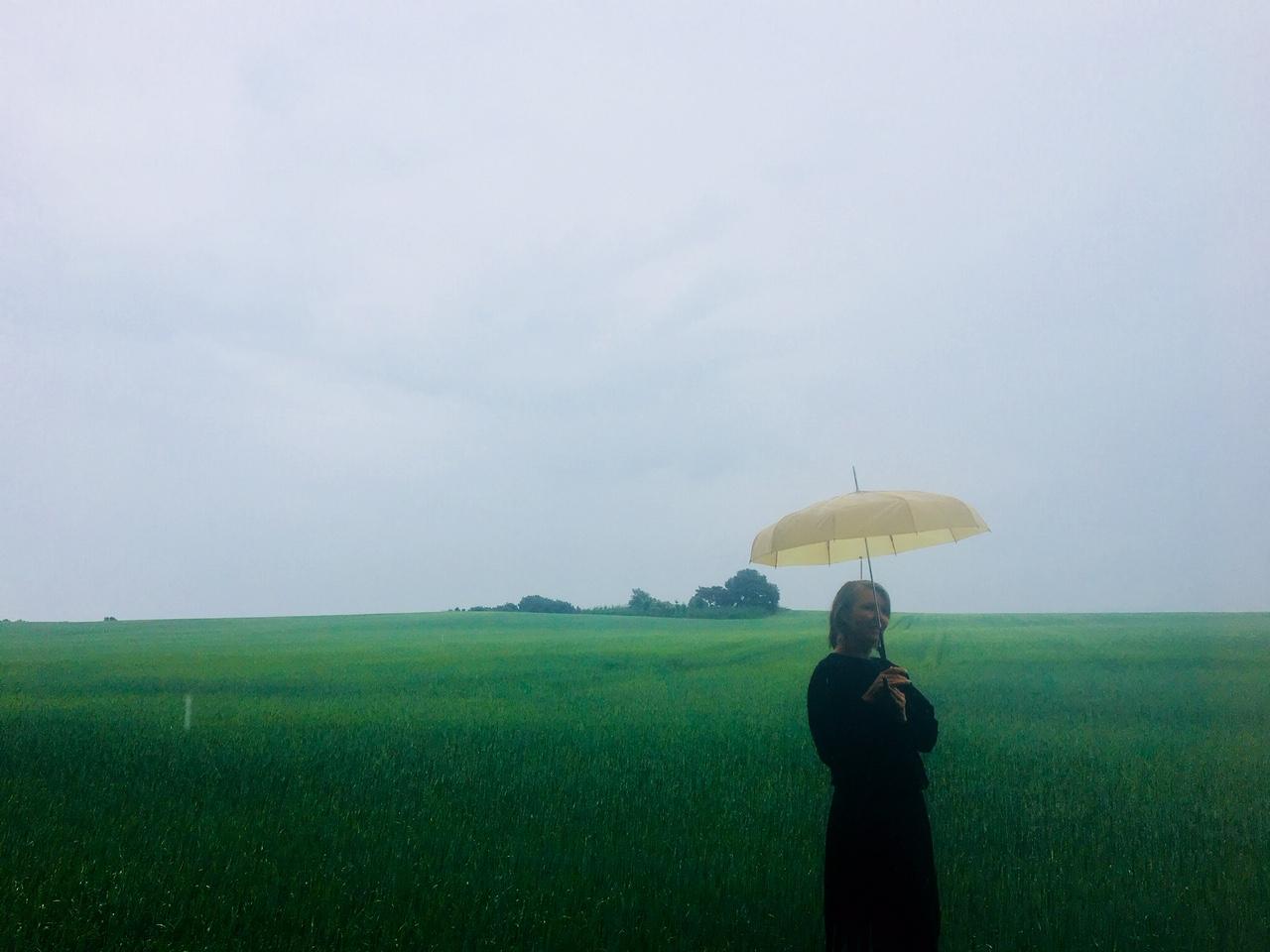 Anja Dalby i regnen på en mark med en gul paraply