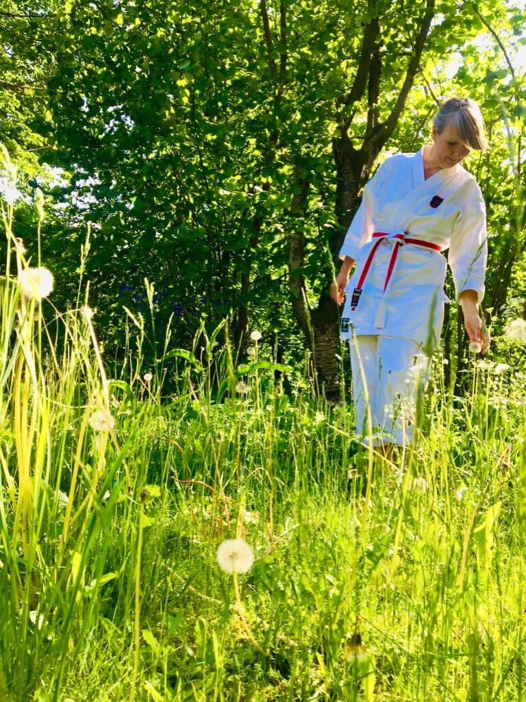 Anja Dalby i naturen, grundsten i en spirituel praksis. Hun står i højt græs med afblomstrede mælkebøtter i sin karatedragt.