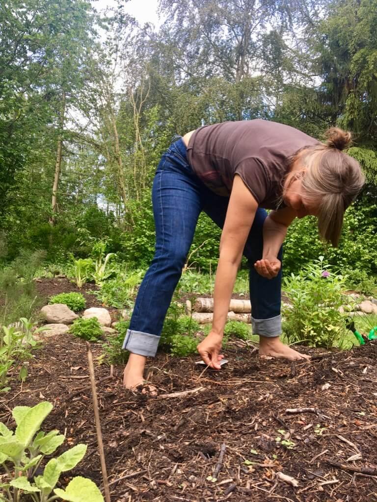 Anja Dalby: Gør du en forskel? Anja i haven ved at plante frø. Står i bare fødder i et bed.