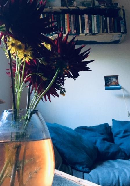Forkæl dit hjem med blomster og hygge. Billede fra Anja Dalbys stue med en vase med blomster i forgrunden og en blød sofa i blå farver i baggrunden.