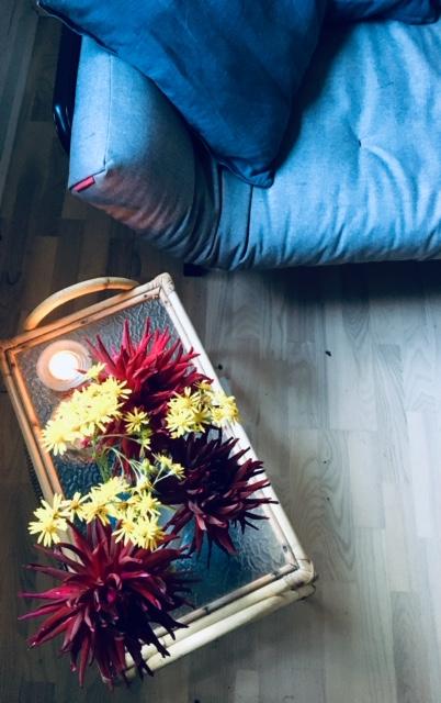 Forkæl dit hjem. F.eks. som her med blomster fra haven på et lille sofabord ved siden af en blå sofa.