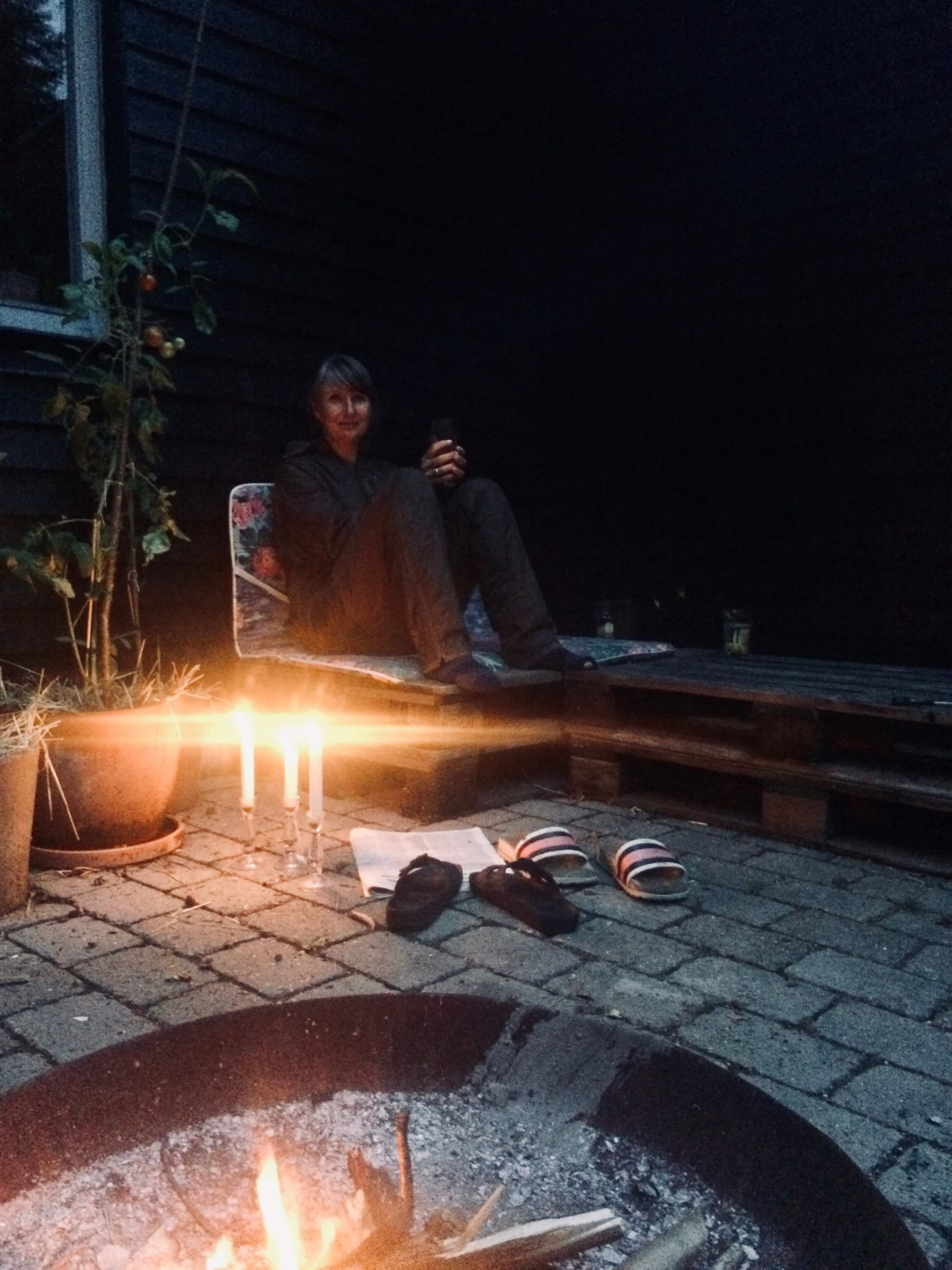 Anja Dalby sidder udenfor sit hus med bål, te og tændte stearinlys.