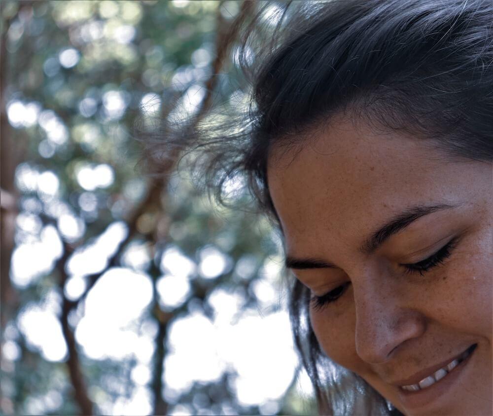 Billede af Carina Lyall, hvor hun smiler med lukkede øjne, mens hun kigger nedad.
