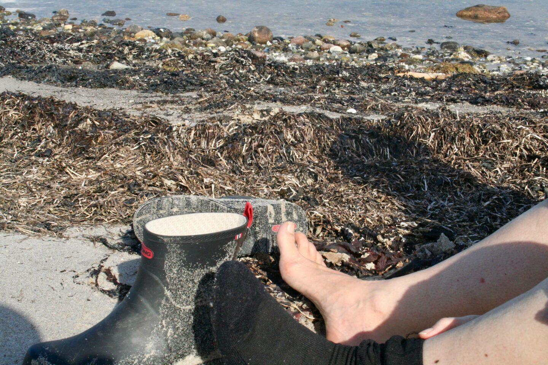 At menneske. At sidde med bare fødder på en tangfyldt strand på Djursland.